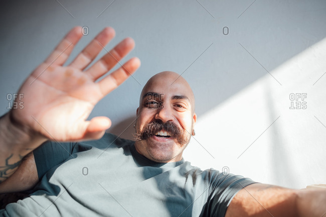 Bald man with moustache self isolating during Corona crisis, smiling and waving at camera.