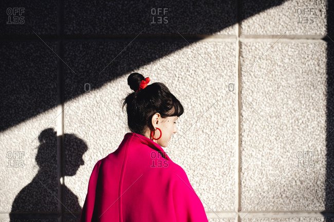 Portrait of woman with dark hair wearing bright red coat in front of concrete wall.