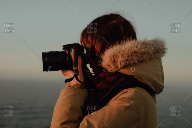 Head and shoulders, woman standing on a cliff, taking photograph with camera.