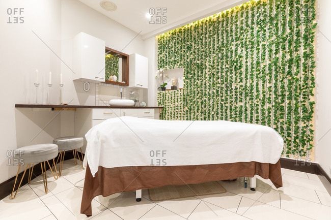 Interior view of room in a beauty salon, with treatment bed, candles, footstools, cupboards and green foliage on one wall.