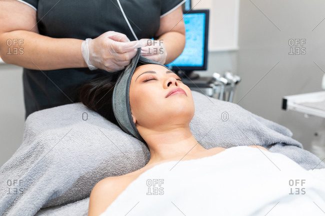High angle view of woman lying on treatment bed in a beauty salon, receiving facial treatment.