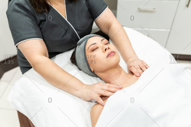 Woman lying on treatment bed in a beauty salon, receiving neck massage.