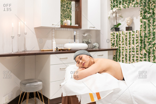 Woman relaxing on treatment bed in a beauty salon.