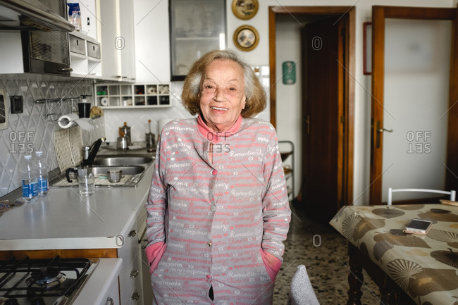 Old woman standing in her kitchen during Corona virus quarantine, smiling at camera.