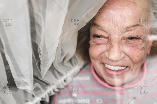 Smiling old woman looking through window during Corona virus quarantine.