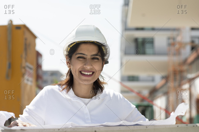Female architect wearing white hard hat working on construction site, smiling at camera.