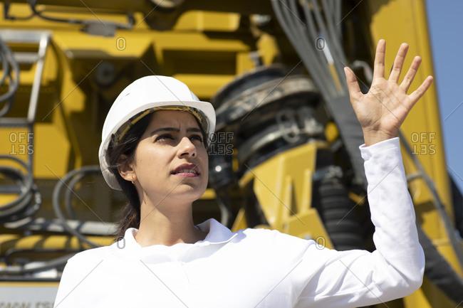 Female architect wearing white hard hat working on construction site.