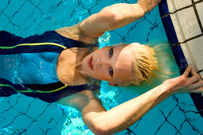 High angle view of blond woman wearing blue swimming costume lying in outdoor swimming pool, looking at camera.