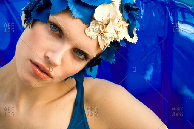 Head and shoulders portrait of blue-eyed woman wearing vintage blue and cream swimming cap.