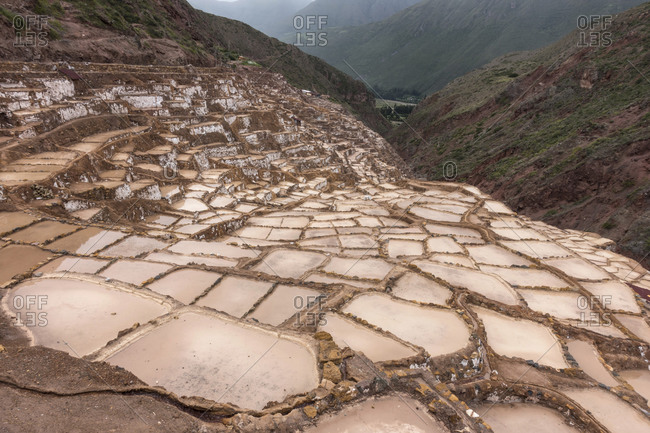 Mountain landscape with Moray Maras terraced salt mine in the foreground near Cusco, Peru.