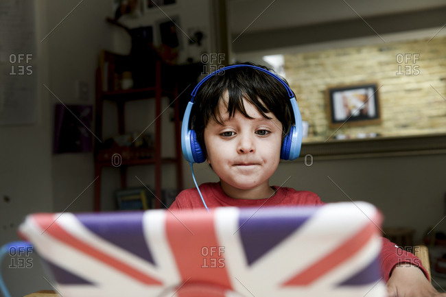A five year old boy in blue headphones having an interactive learning session, home schooling.