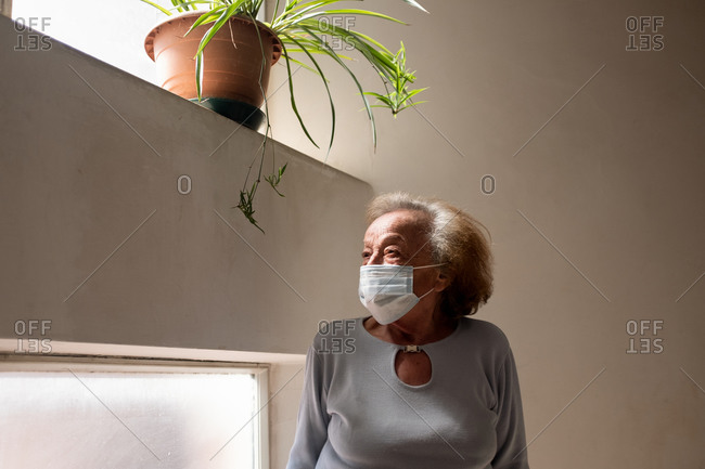 Senior woman wearing face mask standing in her home during Corona virus crisis.