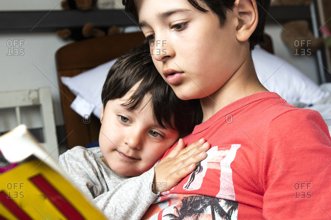 Two brothers sitting on bed, cuddling and reading book.