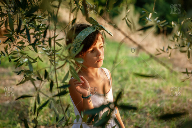 Portrait of girl wearing white summer dress standing under an olive tree in garden.