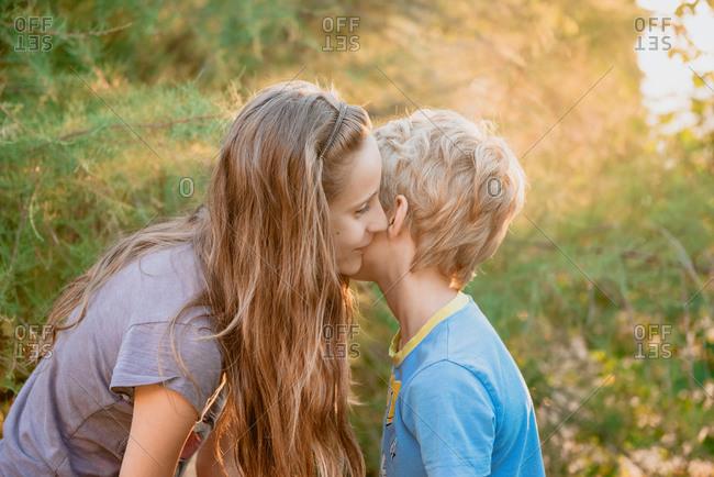 Boy and girl kneeling in a garden, whispering in each others ear.