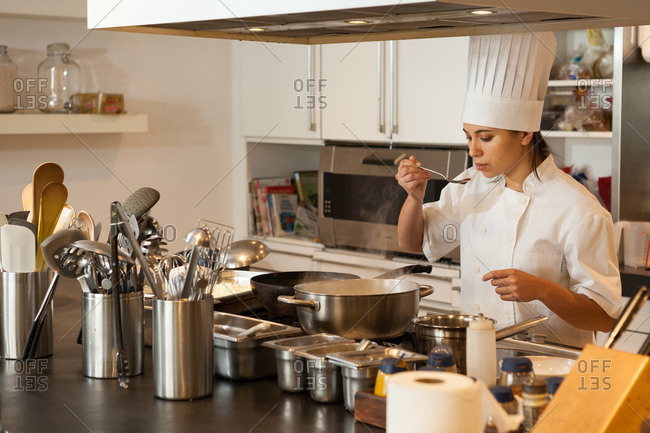 Female chef wearing chef's hat standing at stove in a kitchen, tasting food.