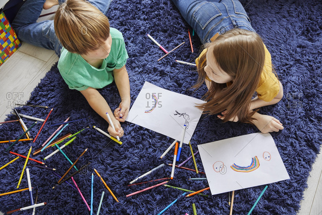 High angle view of boy and girl lying on blue rug, drawing with coloring pencils.