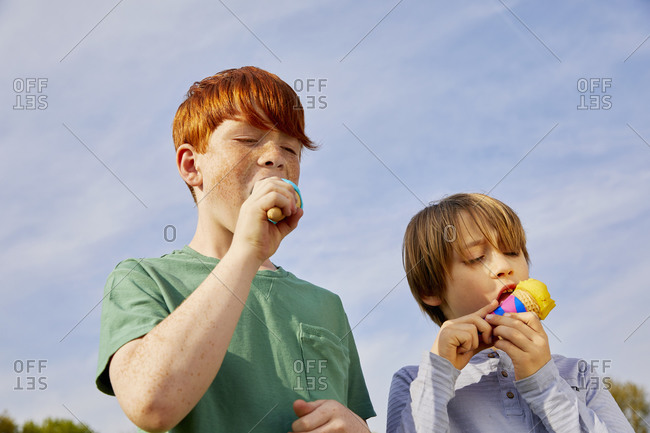 Two boys standing outdoors, eating ice cream cones.