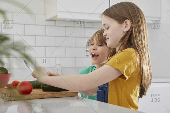 Boy and girl standing in a kitchen, cutting English cucumber and tomato.