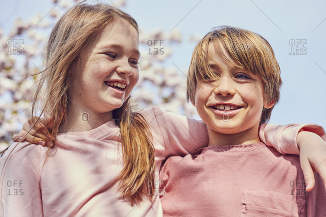 Smiling brunette boy and girl standing outdoors, arms around shoulders.