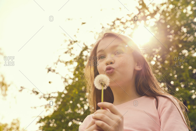 Portrait of smiling girl with long brunette hair standing outdoors, blowing dandelion.