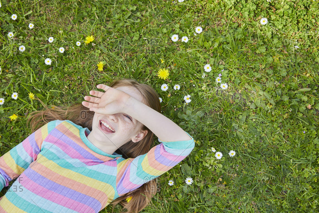 High angle view of girl wearing striped top lying on a spring meadow.