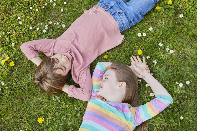 High angle view of boy and girl lying on a spring meadow.