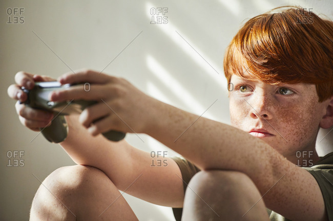 Boy with red hair sitting on floor in sunny room, oldling game console controller.