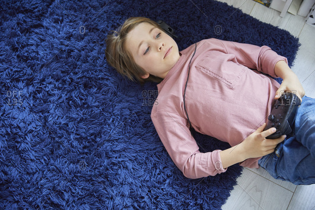 Boy wearing pink T-Shirt lying on his back on blue fluffy rug, holding game console controller.