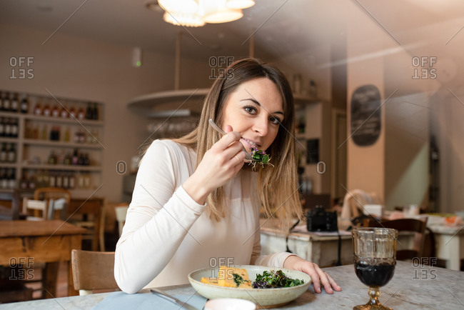 A woman seated at a cafe table eating a dish of vegan food, vegetables on her fork.