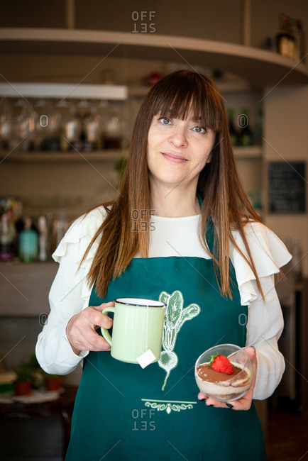 A woman waitress in a vegan cafe, carrying a mug and a dessert with a large strawberry.
