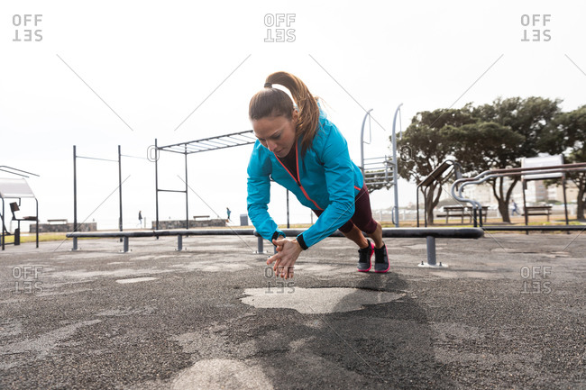 Front view of a sporty Caucasian woman with long dark hair exercising in an outdoor gym during daytime,  in mid air, doing push ups and clapping