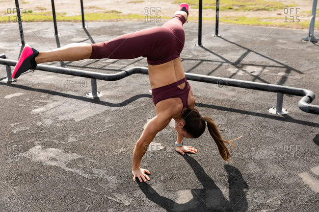 High angle side view of a sporty Caucasian woman with long dark hair exercising in an outdoor gym during daytime, doing handstand, with her legs stretched out.