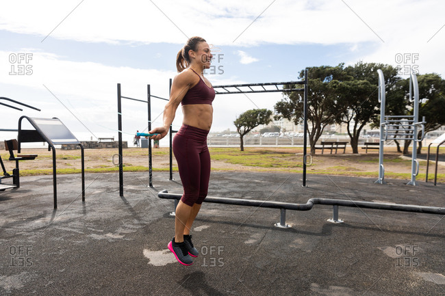 Side view of a sporty Caucasian woman with long dark hair exercising in an outdoor gym during daytime, using a skipping rope, smiling.
