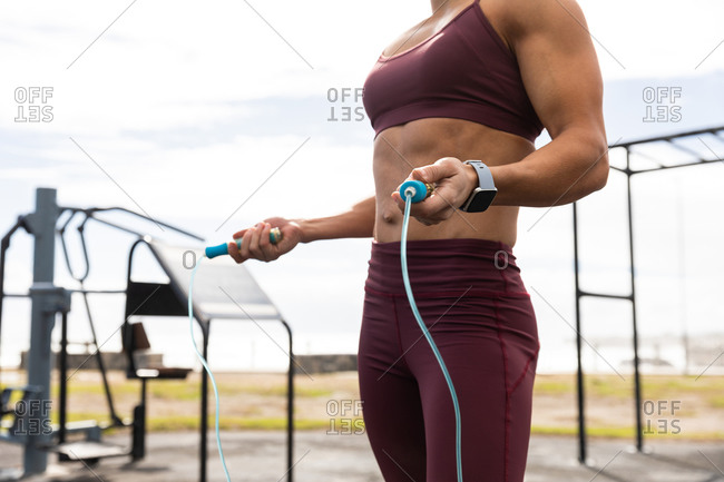 Side view mid section of a sporty Caucasian woman exercising in an outdoor gym during daytime, holding a skipping rope.