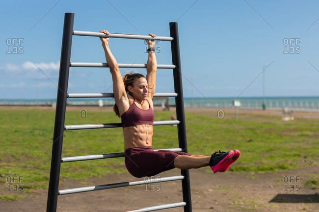 Side view of a sporty Caucasian woman with long dark hair exercising in an outdoor gym by the sea during daytime, hanging off an exercising frame pulling her straight legs up.