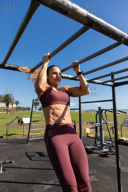 Low angle front view of a sporty Caucasian woman with long dark hair exercising in an outdoor gym during daytime, pulling up an exercising frame.