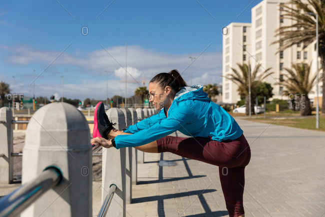 Side view of a sporty Caucasian woman with long dark hair exercising on a promenade by the seaside on a sunny day with blue sky, stretching her leg on a handrail.
