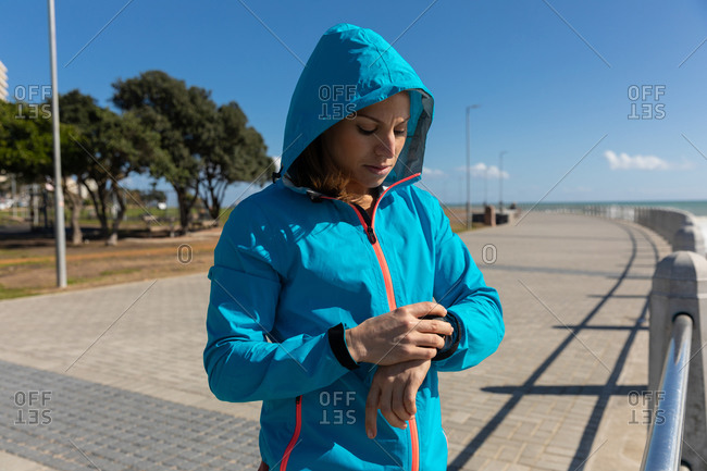 Side view of a sporty Caucasian woman with long dark hair exercising on a promenade by the seaside on a sunny day with blue sky, checking her smartwatch with her hoodie on.