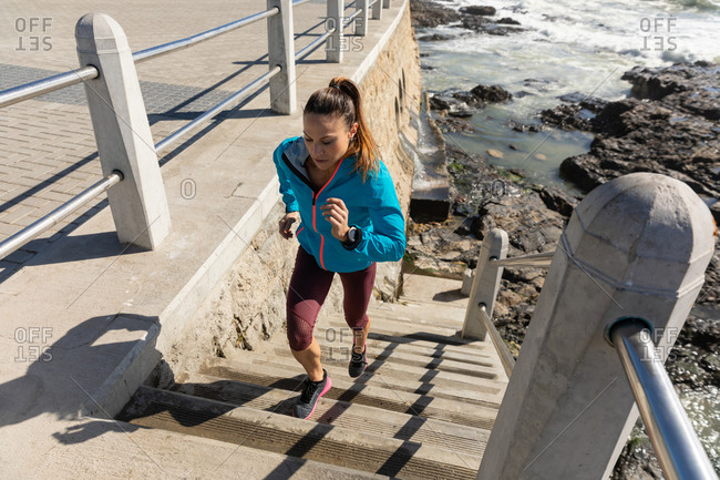 High angle side view of a sporty Caucasian woman with long dark hair exercising on a promenade by the seaside on a sunny day, running up the stairs.