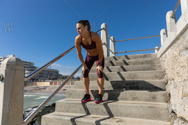 Low angle side view of a sporty Caucasian woman with long dark hair exercising on a promenade by the seaside on a sunny day with blue sky, standing on the stairs, leaning on her knees.