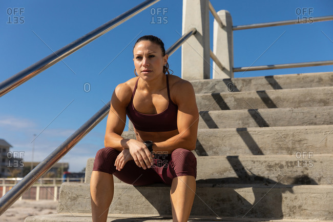 Front view of a sporty Caucasian woman with long dark hair exercising on a promenade by the seaside on a sunny day with blue sky, sitting on the stairs, looking ahead.