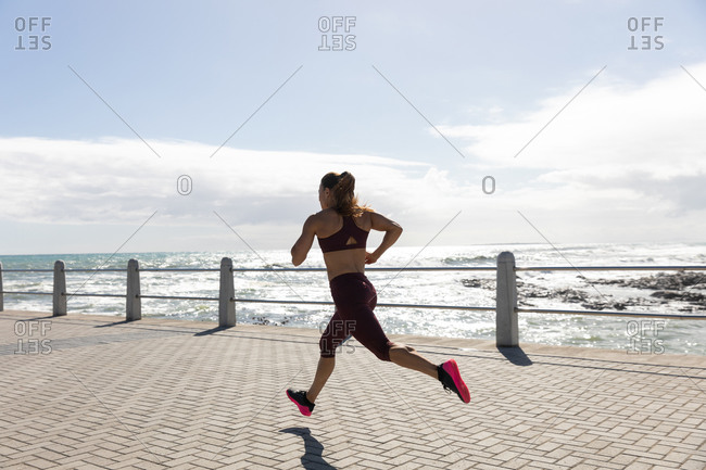Side view of a sporty Caucasian woman with long dark hair exercising on a promenade by the seaside on a sunny day with blue sky, running.