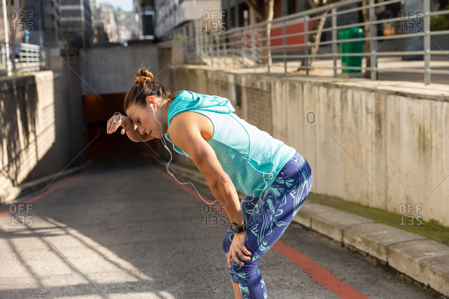 Side view of a sporty Caucasian woman with long dark hair exercising in the urban area on a sunny day, leaning forward with her hands on her knees, wiping the sweat out of her forehead.