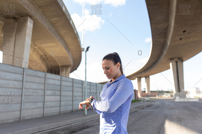 Side view of a sporty Caucasian woman with long dark hair exercising in the urban area on a sunny day, checking her smartwatch.