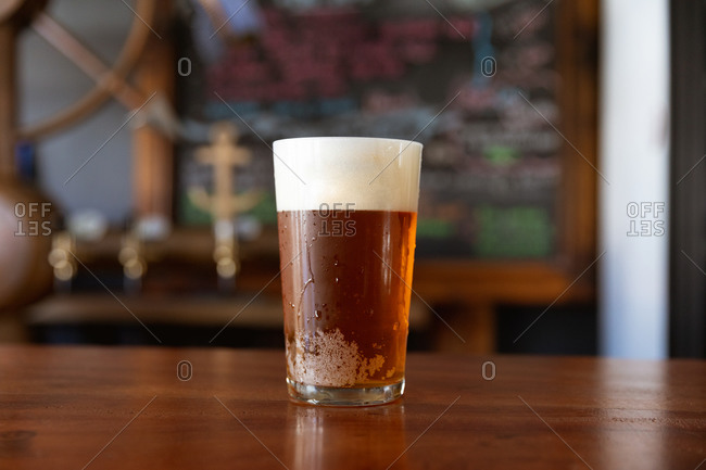 A pint glass of real ale with a head of foam sitting on the wooden bar at a microbrewery pub.