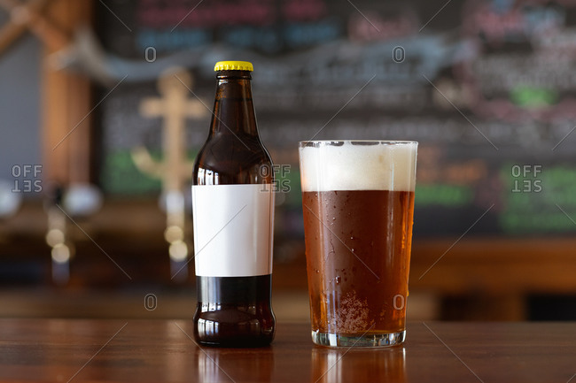 A pint glass of real ale with a head of foam and a glass bottle sitting on the wooden bar at a microbrewery pub.