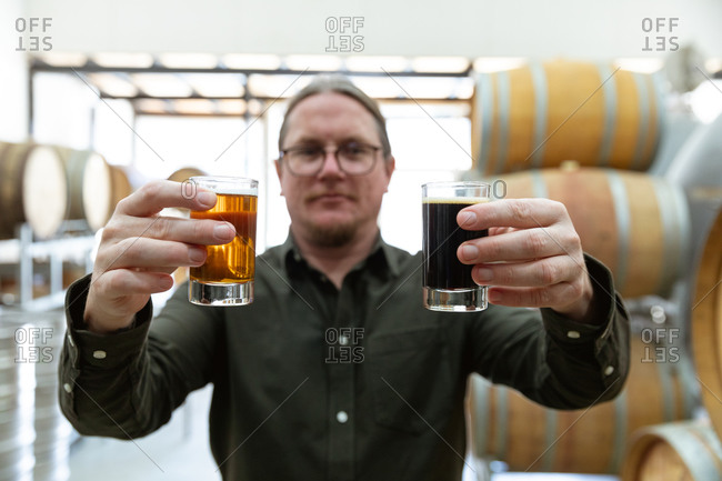 Caucasian man holding two glasses of various kinds of beers in a microbrewery with wooden barrels in the background.