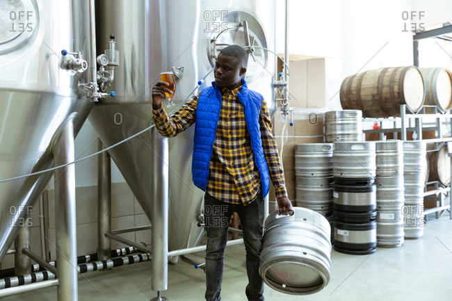 African American man working in a microbrewery, holding a pint of beer and a keg, with vats and wooden barrels in the background.
