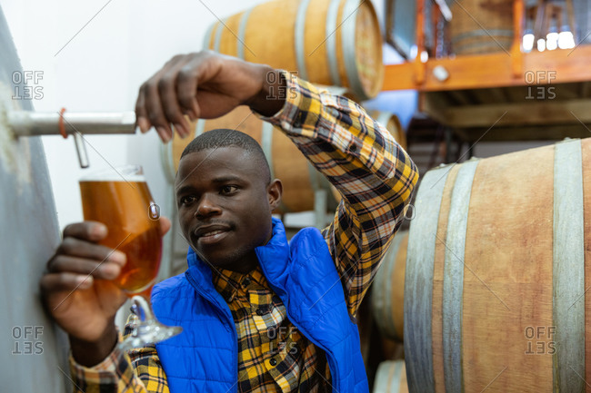 African American man working at a microbrewery pouring beer from a vat into a glass for inspection with wooden barrels in the background.
